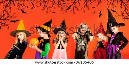 Halloween group of children girls costumes on orange background [Photo Illustration] - stock photo