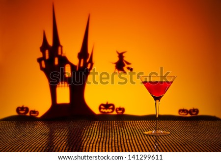 Halloween haunted house witch and a Cosmopolitan cocktail - stock photo