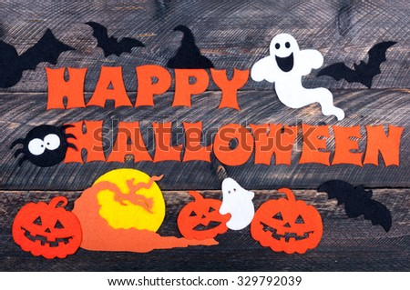 Halloween holiday background. Handmade congratulation word HAPPY HALLOWEEN. Jack lantern, pumpkins, bats, spider, friendly ghosts and full moon made of felt. Halloween decor. Top view - stock photo