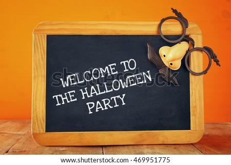 Halloween holiday concept. Blackboard with funny mask, on wooden table