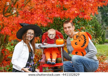 Halloween holiday. little girl blonde in a black hat sitting at a table next to a pumpkin in the garden with parents - stock photo