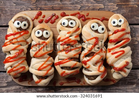 Halloween homemade food sausage meatball mummies wrapped in dough, baked and covered with fake blood sauce decoration for holiday celebration party on vintage wooden background. Rustic style and - stock photo