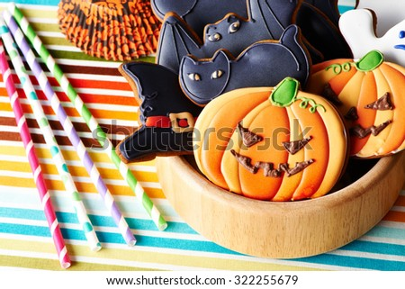 Halloween homemade gingerbread cookies over tablecloth - stock photo