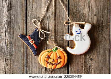 Halloween homemade gingerbread cookies over wooden background - stock photo