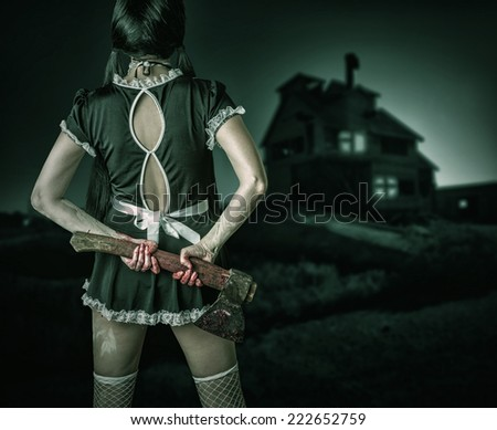 Halloween horror. Dirty woman stands back holding a bloody ax and looks at the old house  outdoor - stock photo