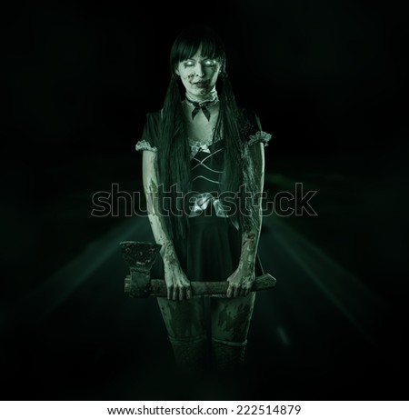Halloween horror. Scary blurred bloody woman ghost with ax on a night road in the headlights - stock photo