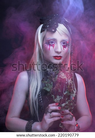 Halloween image. Young woman in black dress and with bloody tears. - stock photo