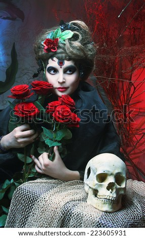Halloween image. Young woman in dramatic artistic image with rose's and skull - stock photo