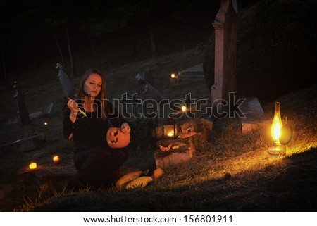 Halloween in the graveyard / Young woman in the light of a lantern - stock photo