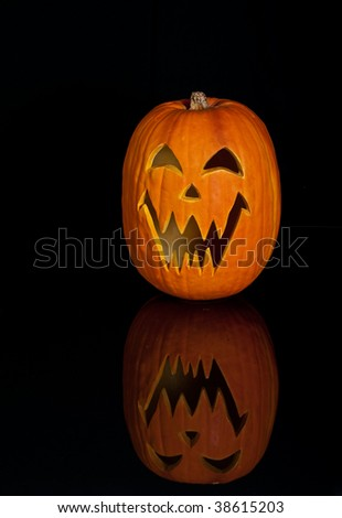Halloween Jack O Lantern already carved and sitting on a table.  One large pumpkin on black with a reflection. - stock photo