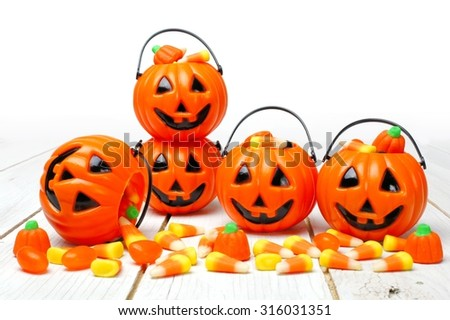 Halloween Jack o Lantern candy holders with scattered candy pumpkins and candy corn on white wood