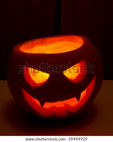 Halloween Jack-'o-Lantern lit from the inside by a candle - stock photo