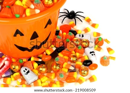 Halloween Jack o Lantern pail overhead view with pile of candy - stock photo