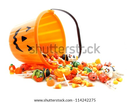 Halloween jack-o-lantern pail with spilling candy over white - stock photo