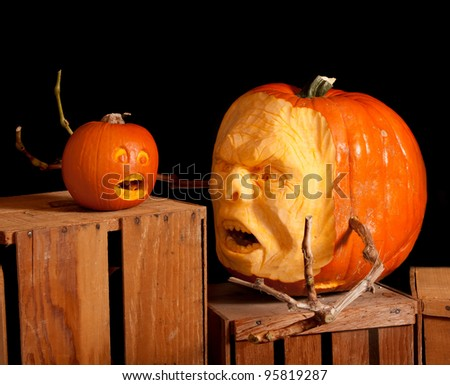 Halloween Jack-o-lantern pumpkin carving very detailed, sitting on wooden crates with a black background - stock photo