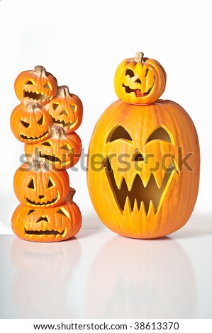 Halloween Jack O Lanterns already carved and sitting on a table.  One large pumpkin and one stack of 6 small pumpkins. - stock photo