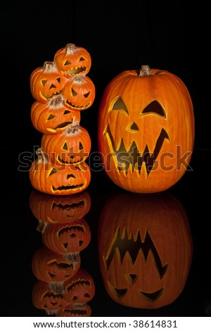 Halloween Jack O Lanterns already carved and sitting on a table.  One large pumpkin and one stack of 6 small pumpkins on black background with reflection. - stock photo