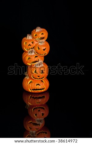 Halloween Jack O Lanterns already carved and sitting on a table.  One large stack of 6 small pumpkins on black with a reflection. - stock photo