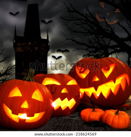 Halloween Jack o Lanterns with spooky tower and tree background - stock photo