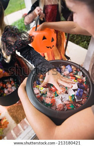 Halloween: Kids Reaching In For Trick Or Treat Candy - stock photo