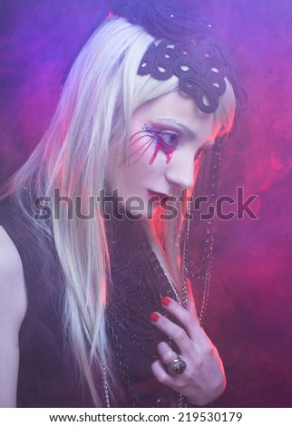 Halloween lady. Young woman in black dress and with bloody tears. - stock photo