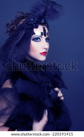 Halloween lady. Young woman in retro style and with feathers in her hair.