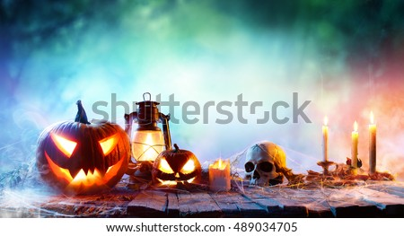Halloween - Lanterns And Pumpkins On Wooden Table In A Haunted Forest