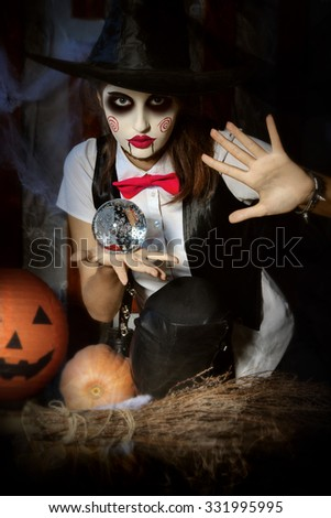 Halloween, mysticism, magic, mystery. Makeup in the style of Billy doll. Girl witch holding a magic ball transparent and casts a spell over him. - stock photo