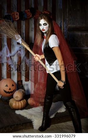 Halloween, mysticism, magic, mystery. Makeup in the style of Billy doll. Witch in a red cape brandishing a broom - stock photo