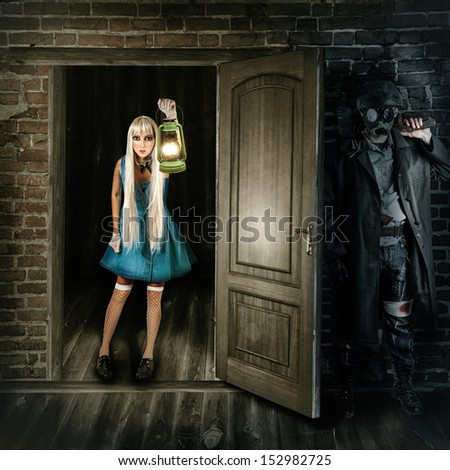 Halloween nightmare concept. Beauty woman with lantern (kerosene lamp) in hand  looks into the room. Male Maniac in mask with axe hiding behind the door - stock photo