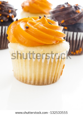 Halloween orange and black cupcakes on white background.