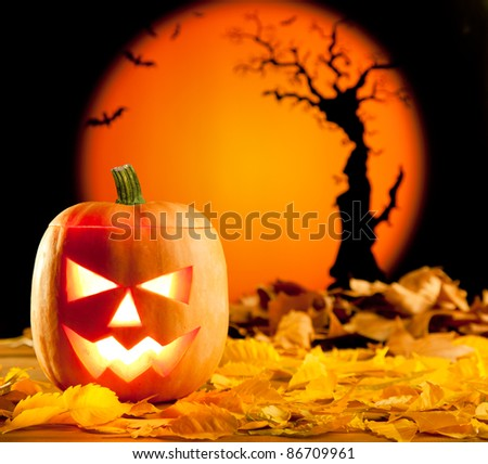 Halloween orange pumpkin lantern with autumn leaves - stock photo