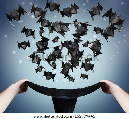 Halloween origami bats fly out of the hat - stock photo