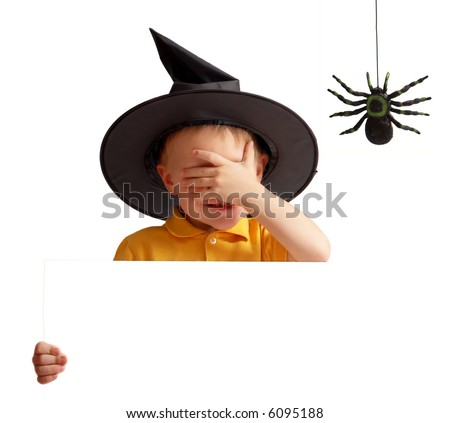 Halloween party only for adults! I am not looking :) Cute playful boy in witch hat with eyes closed by hand holds white banner. - stock photo