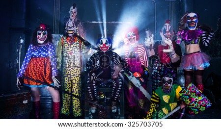 Halloween party scary clowns. Horror clown leader sitting in the electric chair surrounded by terrifying clowns.  - stock photo