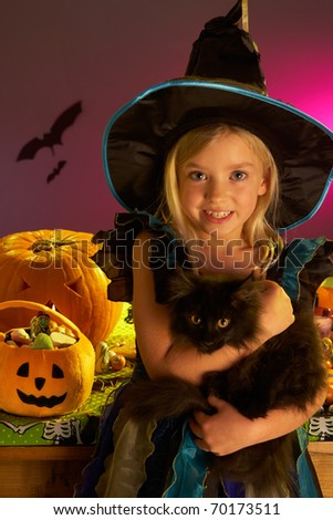 Halloween party with a child holding black cat in hand