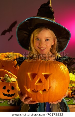 Halloween party with a child holding carved pumpkin - stock photo