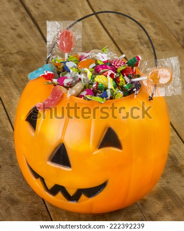 Halloween plastic pumpkin filled with candy on wooden table - stock photo