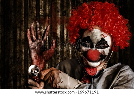 Halloween portrait of a frightening clown doctor holding amputated hand in severe decomposition with medical phonendoscope. Pulse of the maggots - stock photo