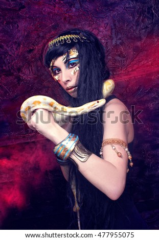 Halloween.  Portrait of egyptian woman posing with white snake.