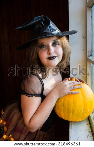Halloween portrait of little girl in black hat and black clothing with pumpkin