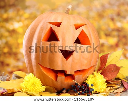 halloween pumpkin and autumn leaves, on yellow background - stock photo