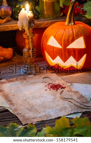 Halloween pumpkin and candle on witch's table - stock photo