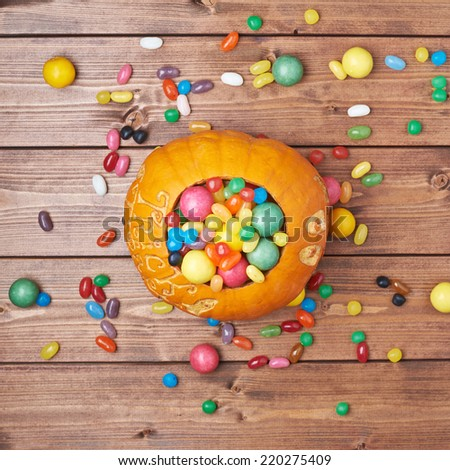 Halloween pumpkin filled with sweets and candies over the wooden board surface, top view above foreshortening - stock photo
