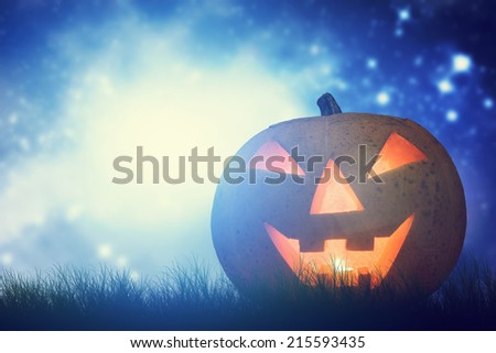 Halloween pumpkin glowing in dark, misty scenery of horror under night starry sky, moon. Hand carved jack o'lantern - stock photo