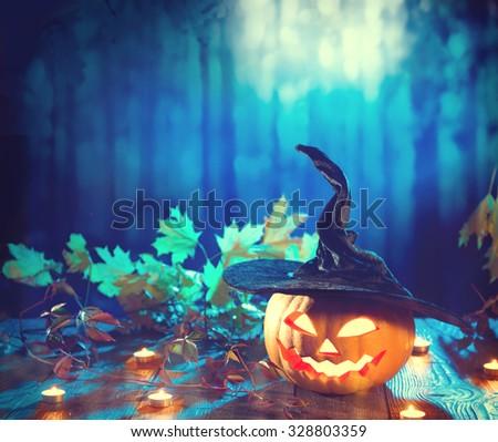 Halloween pumpkin head jack lantern with burning candles. Halloween holidays art design, celebration. Carved Halloween Pumpkins with burning candles in scary deep night forest - stock photo