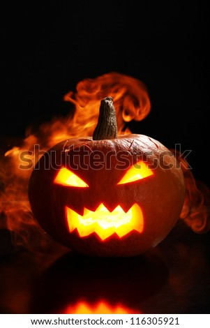 Halloween pumpkin in fire over a black background - stock photo