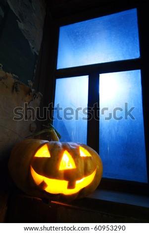 halloween pumpkin in night on old wood room with blue window - stock photo