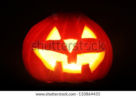 halloween pumpkin jack-o-lantern candle lit, isolated on black background - stock photo