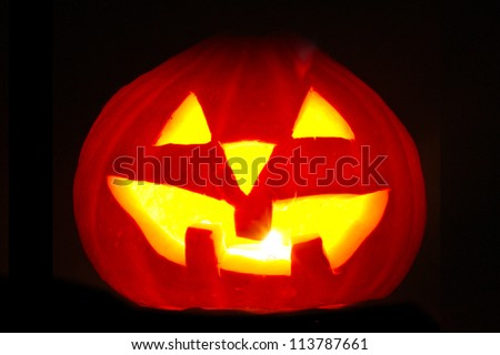halloween pumpkin jack-o-lantern candle lit, isolated on black background - stock photo